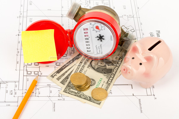 Water meter with pencil and piggy bank on draft Stock photo © cherezoff