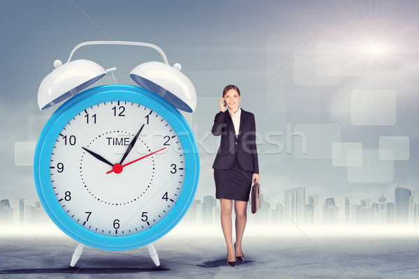 Woman talking on cell phone with big alarm clock Stock photo © cherezoff