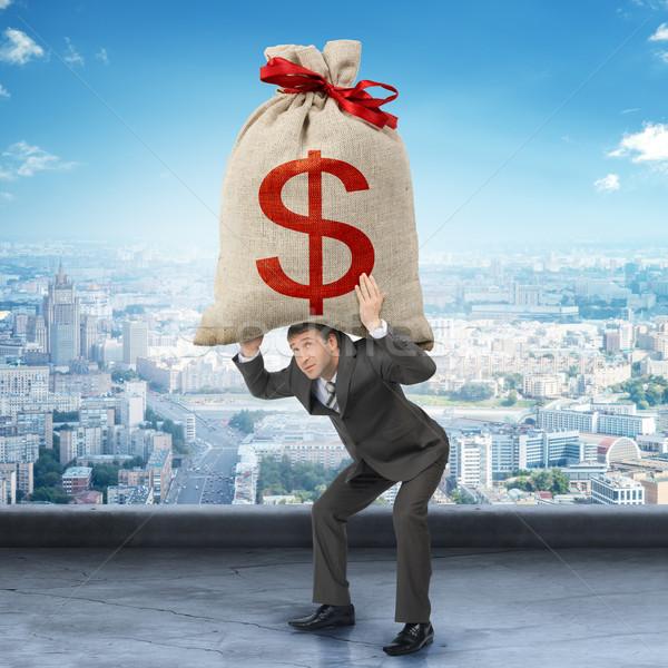 üzletember tart nagy pénzeszsák dollárjel iroda Stock fotó © cherezoff