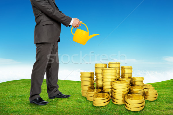 Stock photo: Businessman with can watering coins