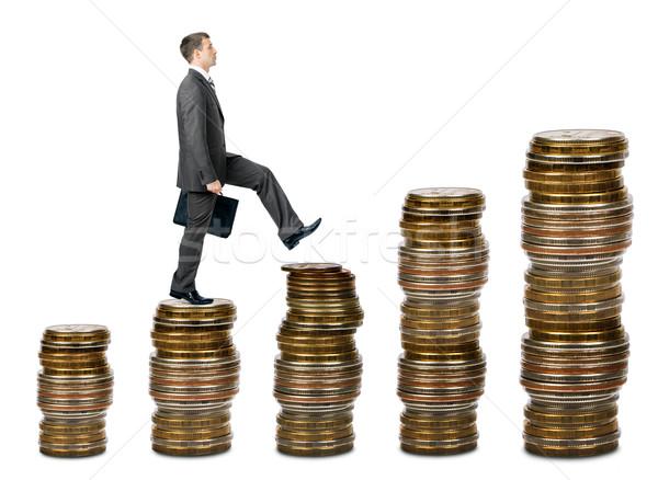 Businessman walking on gold coins Stock photo © cherezoff