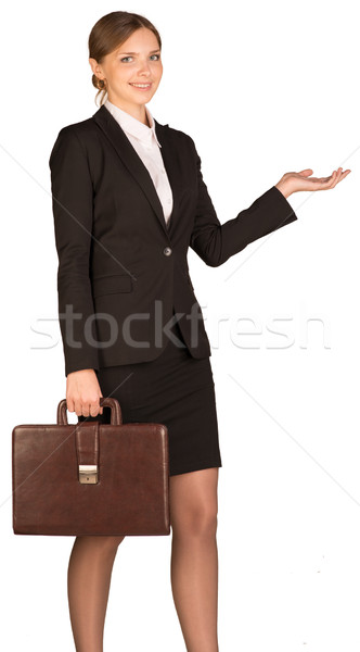Businesswoman holding a briefcase and shows his hand towards Stock photo © cherezoff