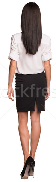 Beautiful businesswomen in blouse and skirt walks forward. Rear view Stock photo © cherezoff