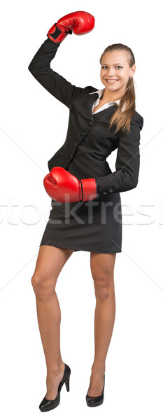 Businesswoman wearing boxing gloves standing with one hand raised, looking at camera, smiling Stock photo © cherezoff