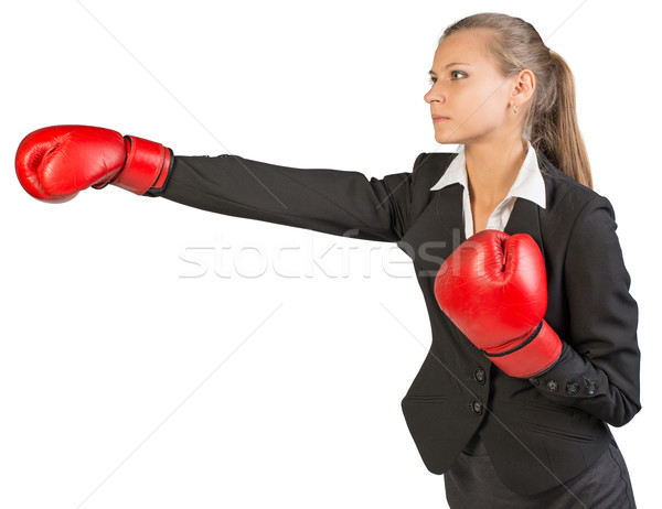 Businesswoman wearing boxing gloves punching Stock photo © cherezoff