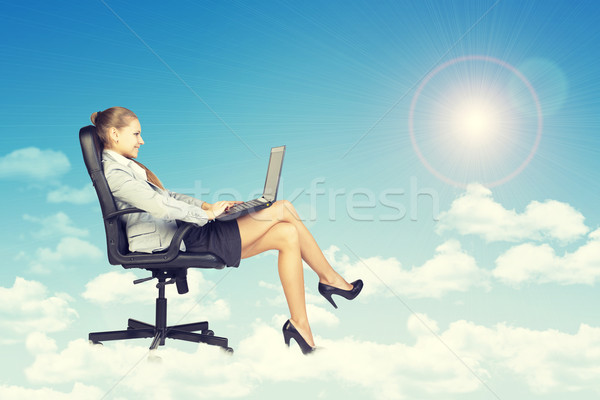 Woman sitting on office chair and holding open laptop, leaning back Stock photo © cherezoff