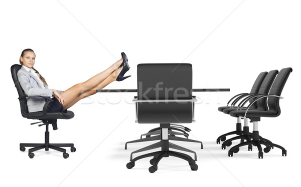 Businesslady sitting in chair with her crossed legs on table Stock photo © cherezoff