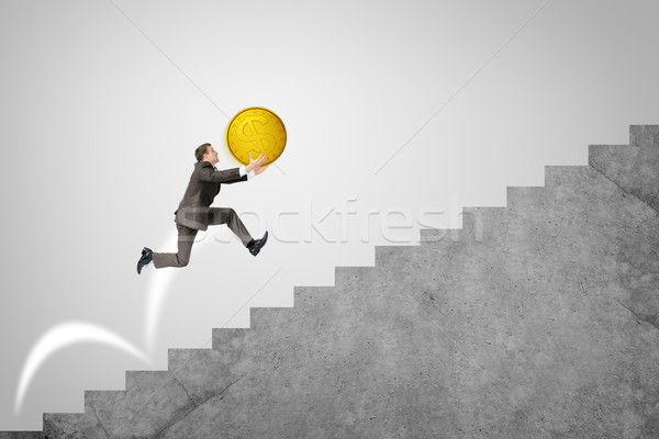 Businessman running up stairs holding big coin Stock photo © cherezoff