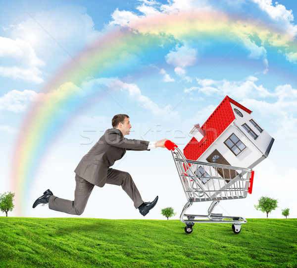 Running businessman with house in shopping cart Stock photo © cherezoff