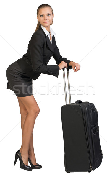 Businesswoman bending forward leaning on extended handle of wheeled suitcase Stock photo © cherezoff