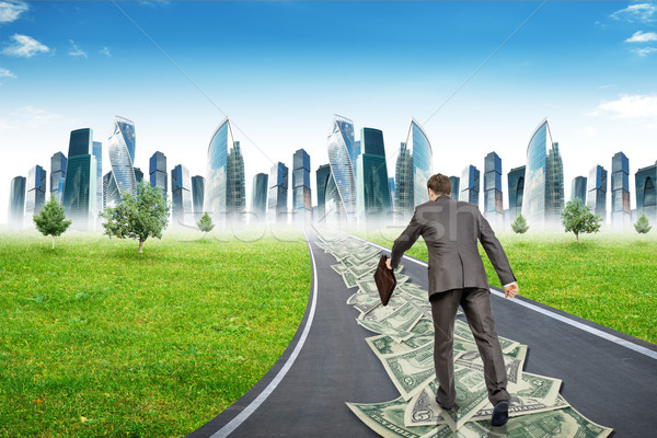 Businessman with suitcase on money road Stock photo © cherezoff