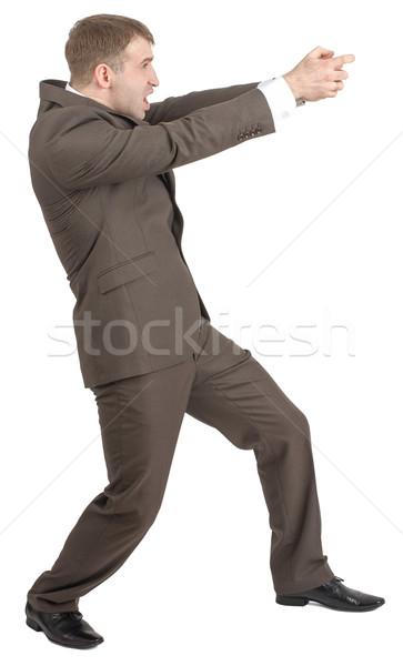 üzletember tart láthatatlan fegyver nyitva száj Stock fotó © cherezoff