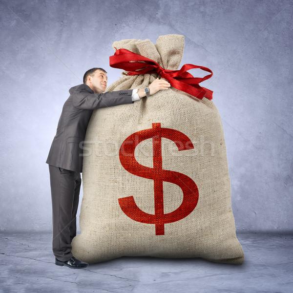 Businessman hugging bag with dollar sign Stock photo © cherezoff