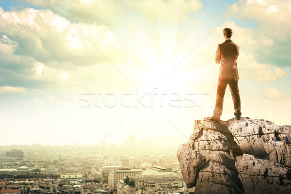 Young businessman standing on edge of rock Stock photo © cherezoff