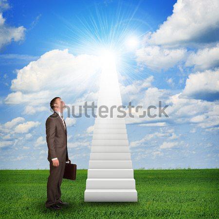 Businessman climbing up stairs leading to sky Stock photo © cherezoff