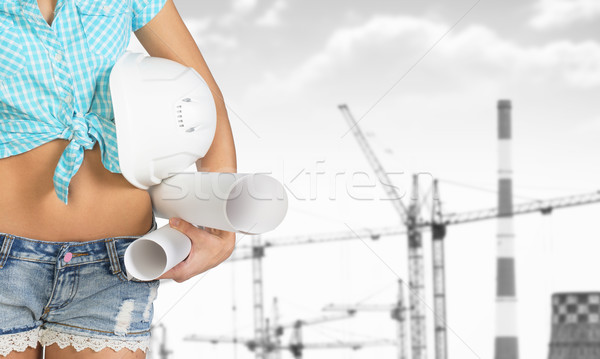 Woman holding helmet and paper. Cranes with heat power stations on background Stock photo © cherezoff