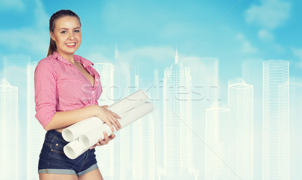 Woman in short jeans holding rolls of paper, smiling. Wire-frame buildings as backdrop Stock photo © cherezoff