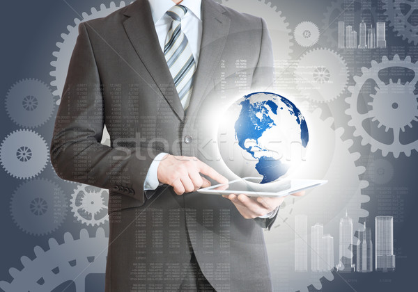 Businessman using tablet with planet Stock photo © cherezoff