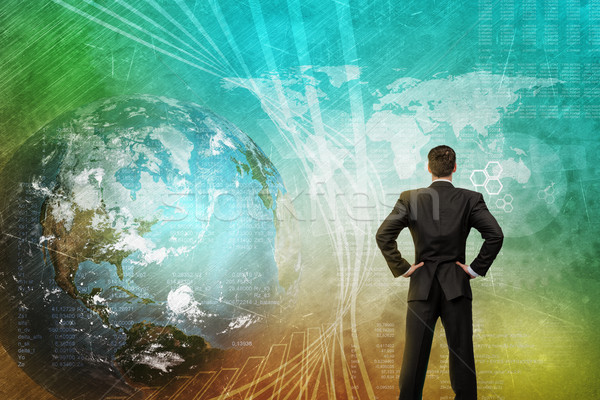 Businessman in front of holographic screen Stock photo © cherezoff