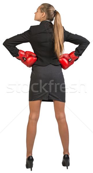 Businesswoman wearing boxing gloves standing akimbo Stock photo © cherezoff