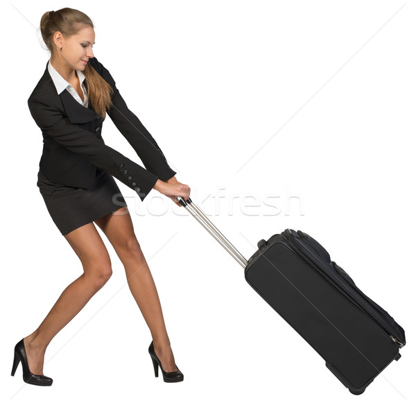 Businesswoman dragging heavy wheeled suitcase with both hands Stock photo © cherezoff