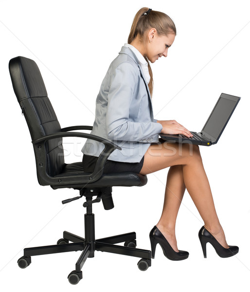 Businesswoman on office chair operating laptop  Stock photo © cherezoff