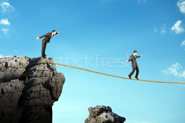 Stock photo: Businessman walking on rope above gap
