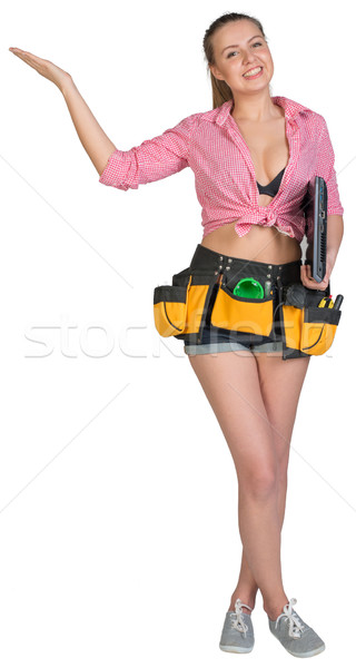 Woman in tool belt, with laptop under her armpit, showing empty palm Stock photo © cherezoff