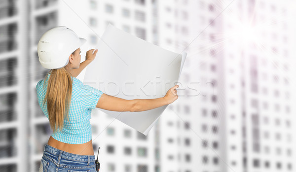 Woman in helmet standing backwards and holding paper sheet. Building with windows as backdrop  Stock photo © cherezoff