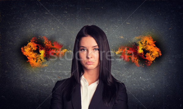 Sad woman with fire from ears. Concrete gray wall as backdrop Stock photo © cherezoff