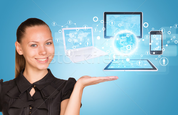 Beautiful businesswoman demonstrating computer equipment. Stock photo © cherezoff