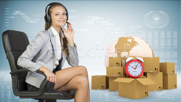 Businesswoman in headset, sitting on office chair. Globe, commodity boxes and alarm-clock beside Stock photo © cherezoff