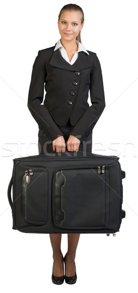 Businesswoman holding suitcase, looking at camera, smiling Stock photo © cherezoff