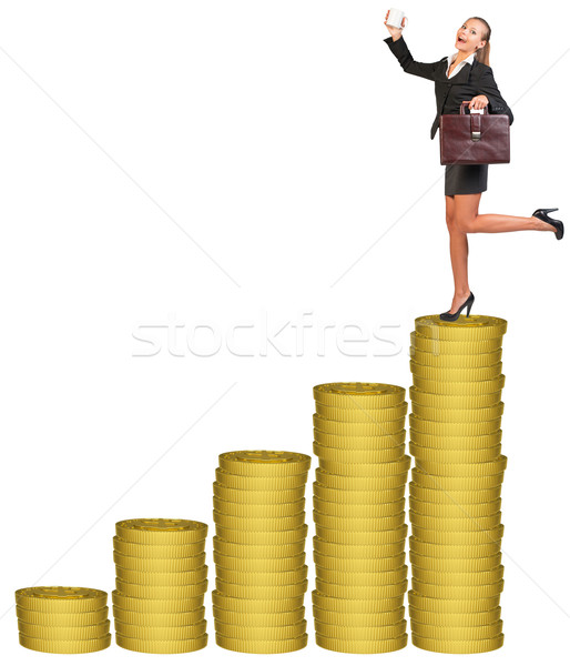 Businesslady with suitcase on gold coins stack  Stock photo © cherezoff