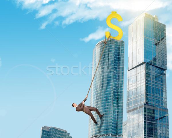 Businessman climbing skyscraper Stock photo © cherezoff