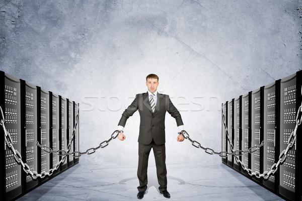 Businessman chained to iron boxes Stock photo © cherezoff