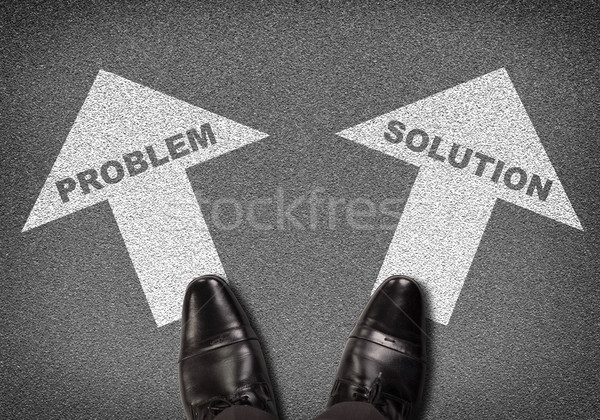 Shoes standing on asphalt road with two arrows. Labels problem and solution Stock photo © cherezoff