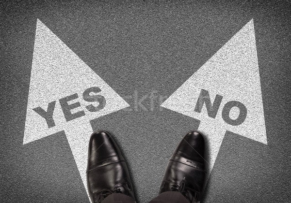 Shoes standing on asphalt road with two arrows. Labels YES and NO Stock photo © cherezoff