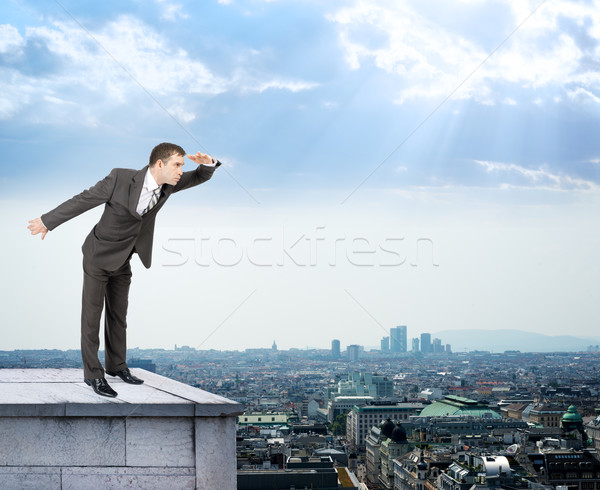 Businessman looking forward on building roof Stock photo © cherezoff