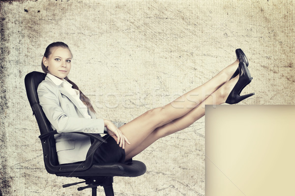 Businesswoman in office chair with her feet up on anything Stock photo © cherezoff
