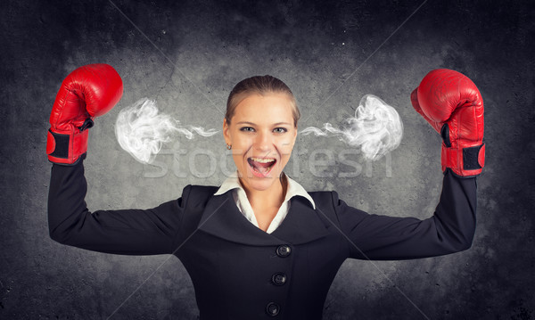 Businesswoman in boxing gloves posing with her arms up, shouting, smoke from ears Stock photo © cherezoff