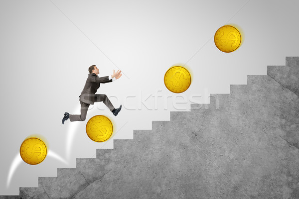 Businessman running up stairs with gold coins Stock photo © cherezoff