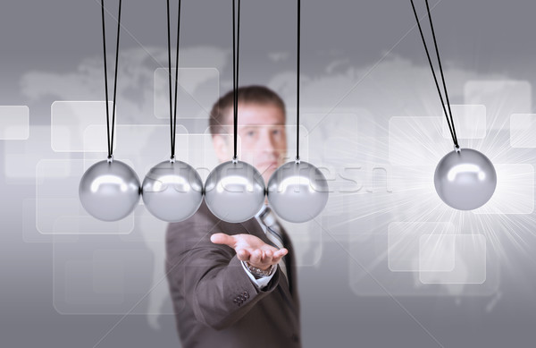 Businessman in suit hold Newtons cradle Stock photo © cherezoff