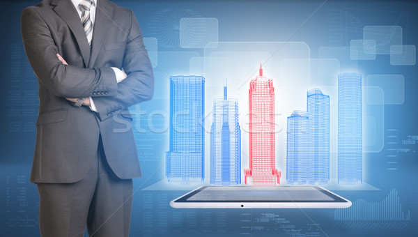 Businessman and wire-frame buildings on screen tablet pc Stock photo © cherezoff