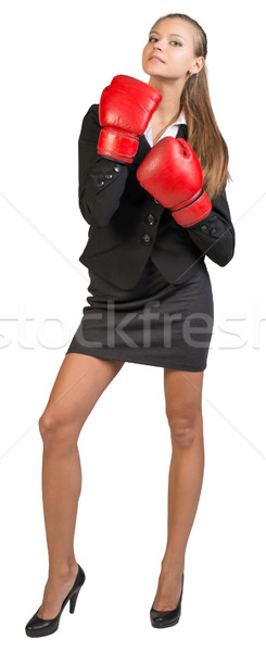 Businesswoman wearing boxing gloves, looking ahead and upwards Stock photo © cherezoff