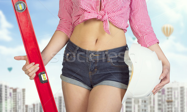 Woman in short jeans holding spirit level and helmet. Buildings as backdrop Stock photo © cherezoff