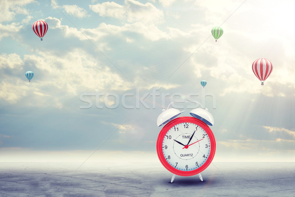 Alarm clock on concrete floor with background of clouds, hot air balloon Stock photo © cherezoff