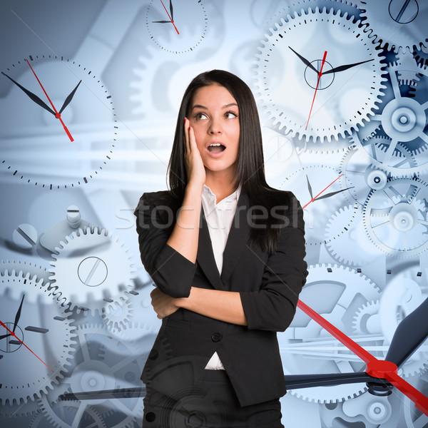 Surprised businesslady with clocks Stock photo © cherezoff