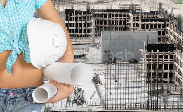 Smiling young woman holding hard hat and paper scrolls Stock photo © cherezoff