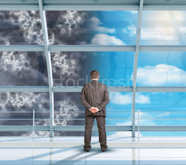 Businessman looking at changing weather Stock photo © cherezoff